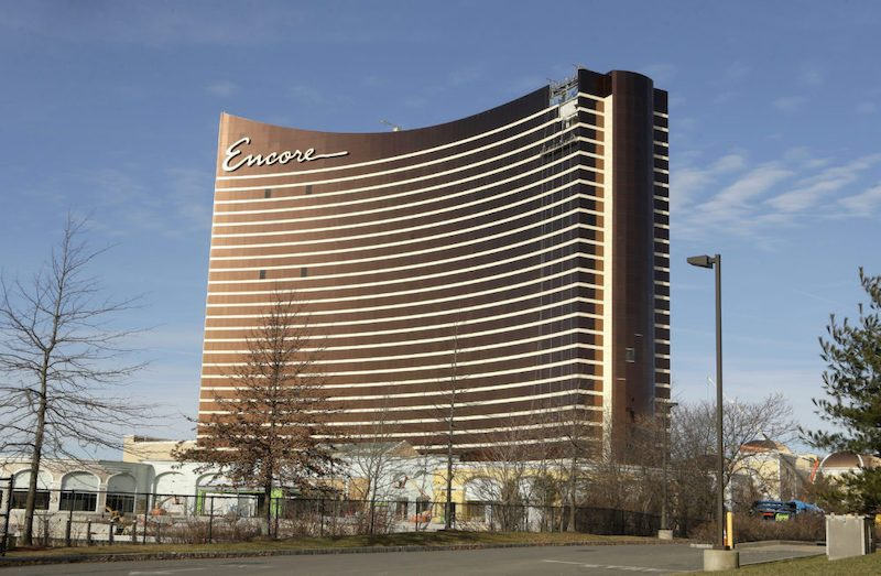 In this Wednesday, Jan. 2, 2019 photo the under-construction Encore Boston Harbor luxury resort and casino stands among smaller structures, in Everett, Mass. A Nevada judge was being asked Friday, Jan. 4 to let the Massachusetts Gaming Commission make public a report on allegations of sexual misconduct against former casino mogul Steve Wynn. A decision could affect a decision on a pending license for the $2 billion casino and hotel being built in Everett. (AP Photo/Steven Senne)