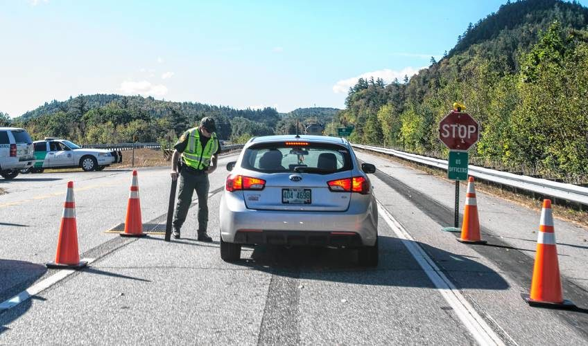 A U.S. Border Patrol agent checks a car on the I-93 southbound lane on Wednesday, September 28, 2017 south of the Route 175 exit south of Lincoln.