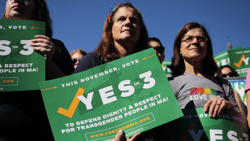 Boston, MA - 9/16/2018 -  Camille Ernst (middle) and Joanne Hooker (right) hold signes for a