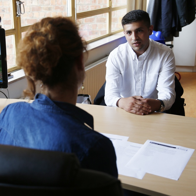Unemployed Belgian Mohamed Sammar (R) answers questions during a simulated job interview, which is recorded to help him get feedback afterwards in Brussels July 2, 2013. Sammar, 27, has been looking for a job in the construction sector for 2 years.