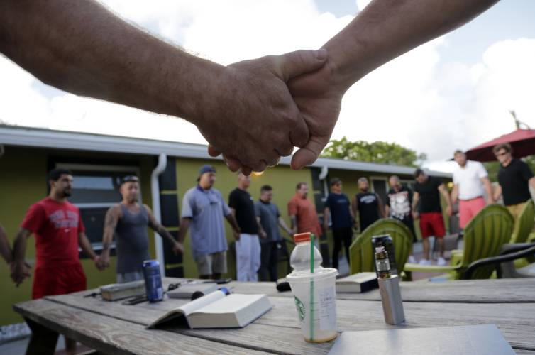 In this Thursday, July 6, 2017 photo, recovering addicts join hands during a meeting at Recovery Boot Camp, in Delray Beach, Fla. The center is run by Timothy Schnellenberger, who has operated treatment centers since 2002. He says that the influx of criminal operators has cast a dark shadow over an industry with deep roots in South Florida. (AP Photo/Lynne Sladky)