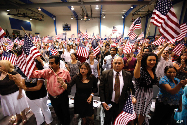 People hold flags as they are sworn in as U.S. citizens during a naturalization ceremony on Tuesday, July 2, 2010 in Phoenix. (AP Photo/Rick Scuteri)