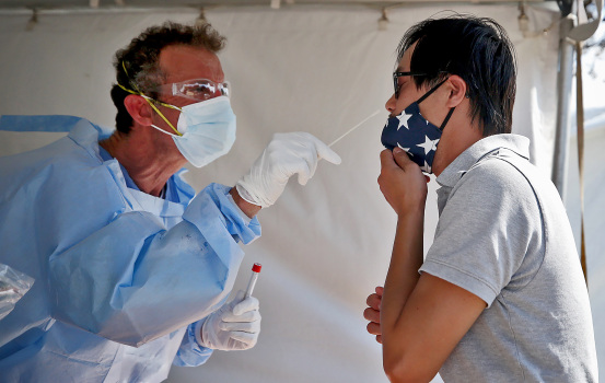 BOSTON MA. - AUGUST 5: Matthew Norcia, RN, performs a Covid test on Nick Le on Columbia Rd in Southie on August 5, 2020 in Boston, MA. (Staff Photo By Nancy Lane/MediaNews Group/Boston Herald)